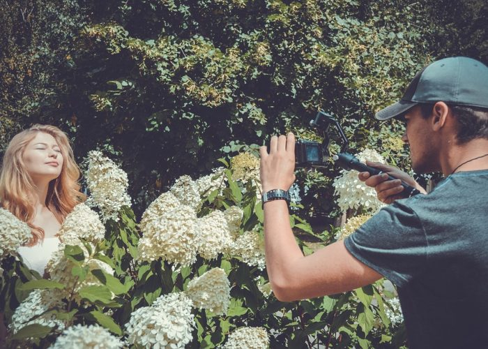 Man taking photo of women next to flowers