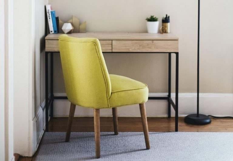 green chair in front of a wooden desk